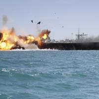 In this picture released by the Iranian Tasnim news agency on Wednesday, a replica of a U.S. aircraft carrier is exploded by the Revolutionary Guard's speedboats during large-scale naval drills near the entrance of the Persian Gulf, Iran. The drill, named Great Prophet 9, was the first to involve a replica of a U.S. carrier. | AP