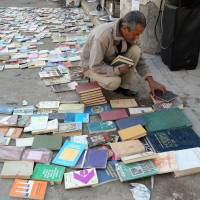 An Iraqi looks at books on central Baghdad's al-Mutanabi Street, home to the city's book market, on Jan. 23. | AP