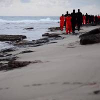 An image grab taken from a video released by the jihadist media arm Al-Hayat Media Centre on Sunday purportedly shows black-clad Islamic State group fighters leading handcuffed hostages, said to be Egyptian Coptic Christians, wearing orange jumpsuits before their alleged decapitation on a seashore in the Libyan capital of Tripoli. | AFP-JIJI/HO/AL-HAYAT MEDIA CENTRE