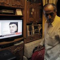 Said Musallam, an Israeli Arab whose son, Muhammad, is being held by Islamic State in Syria as an alleged spy, watches television reports about him in their East Jerusalem home on Thursday. Islamic State said on Thursday it was holding Muhammad Musallam, who had posed as a foreign fighter in order to spy for Mossad, an account denied by Israel and by his family, who said he had been kidnapped. | REUTERS