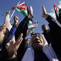 Jordanians chant slogans to show their support for the government against terror as they were waiting for Jordan's King Abdullah II, returning from the U.S., at Queen Alia Airport in Ammanon Wednesday. King Abdullah II rushed home Wednesday, cutting short a U.S. trip, to rally public support for even tougher strikes against the Islamic State group after the militants released a video showing the captured Jordanian pilot being burned to death in a cage. | AP