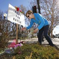 Turi Whiting of Minneapolis leaves a bouquet of flowers Monday at a 'Pray for Kayla' sign in downtown Prescott, Arizona. Mueller, a 26-year-old American woman held by Islamic State militants, has been confirmed dead, her parents and the Obama administration said Tuesday. The White House said that Mueller's family received a private message from her captors over the weekend and the information contained in that communication was authenticated by the U.S. intelligence community. It was not immediately clear how and when Mueller died. | AP