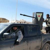 In this image posted on a militant social media account by the Al-Baraka division of the Islamic State group on Tuesday, Islamic State militants ride in a Kurdish popular protection unit (YPG) vehicle captured during fighting in Tal Tamr, Hassakeh province, Syria. Fierce fighting between Kurdish and Christian militiamen and Islamic State militants raged on Wednesday, with the jihadis reportedly losing ground. | AP