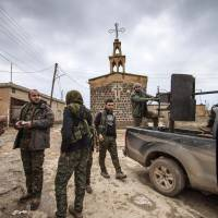Fighters from the Kurdish People's Protection Units (YPG) stand near a pickup truck mounted with an anti-aircraft weapon in front of a church in the Assyrian village of Tel Jumaa, north of Tel Tamr town, on Feb. 25, 2015. Kurdish militia launched an offensive against the Islamic State group in northeast Syria on Wednesday, cutting one of its supply lines from Iraq, as fears mounted for dozens of Christians abducted by the jihadi group.   REUTERS