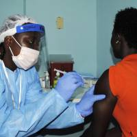 A health worker injects a woman with an Ebola vaccine in Monrovia on Monday as Liberia carries out a trial of experimental Ebola vaccines involving thousands of volunteers as part of an effort to slow the spread of the deadly fever and prevent future outbreaks. | REUTERS