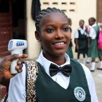 A student has her body temperature checked as part of an Ebola screening at Don Bosco High School as schools reopen in the Liberian capital Monrovia on Monday. Children trickled back to school in Liberia after the restart of lesson, as the country begins to turn the page on the crisis. | AFP-JIJI