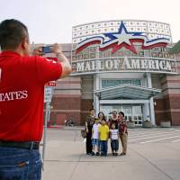 Visitors pose for a family photograph in front of an entrance to the Mall of America in Bloomington, Minnesota, in  July 2013. U.S. homeland security chief Jeh Johnson said Sunday he takes seriously a threat made by Somali-based Islamist militants against shopping malls, including the Mall of America. | REUTERS