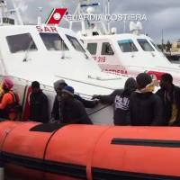 Migrants disembark Tuesday from a boat from the Italian coast guard after a rescue operation off the coast of Lampedusa Monday. Twenty-nine African migrants intercepted by Italian authorities while trying to reach Europe by boat in rough and icy conditions  have died of hypothermia, most after being rescued, sources told AFP. Coast guard speedboats picked up 105 migrants in the Mediterranean overnight, seven of whom were already dead, from a converted fishing boat battered by high winds and waves that hit 8 meters. | AFP-JIJI
