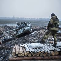 A pro-Russian rebel guards a captured former Ukrainian Army checkpoint outside Vuhlehirsk in the Donetsk region in eastern Ukraine on Thursday. | AP