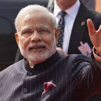 Indian Prime Minister Narendra Modi wears a dark pinstriped suit with his name monogrammed in dull gold stripes during a reception for U.S. President Barack Obama in New Delhi on Jan.25. The suit, which became controversial after photographs of it went viral on social media, has been auctioned for around $690,000 in Modi's home state of Gujarat. | AP