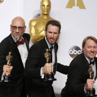 Ron Conli (left), Chris Williams (center) and Don Hall pose with their award for best animated feature film for 'Big Hero 6' during the 87th Academy Awards in Hollywood on Sunday. Most laureates were white, a fact pointed out in near-to-the-bone humor by some speakers. | REUTERS