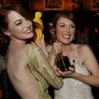 Actress Emma Stone (left) compares her Lego Oscar statuette with actress Julianne Moore's genuine Oscar for best leading actress for her role in 'Still Alice' at the Governors Ball following the 87th Academy Awards in Hollywood, California, on Sunday. | REUTERS