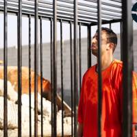 This still image made from video released by Islamic State group militants and posted on the website of the SITE Intelligence Group on Tuesday purportedly shows Jordanian pilot Lt. Mu'ath al-Kaseasbeh standing in a cage just before being burned to death by his captors. The death of the 26-year-old pilot, who fell into the hands of the militants in December when his Jordanian F-16 crashed near Raqqa, Syria, followed a weeklong drama over a possible prisoner exchange.   AP