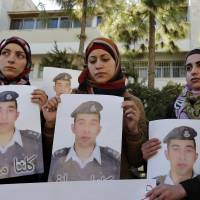 Anwar Tarawneh (center), the wife of Jordanian pilot Mu'ath al-Kaseasbeh, holds a picture of her husband during a student-led rally calling for his release at Jordan University in Amman on Tuesday.   REUTERS