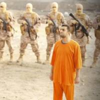 A man purported to be Islamic State captive Mu'ath al-Kaseasbeh (front) is shown standing in front of armed men in a still image taken from an undated video of his execution. The video was released on social media on Tuesday.   REUTERS