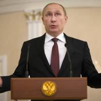 Russian President Vladimir Putin speaks to the media in Minsk on Thursday following peace talks about the Ukraine conflict.   AP