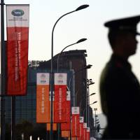 A paramilitary police officer stands in front of banners for the Asia-Pacific Economic Cooperation forum displayed outside the China National Convention Center in Beijing in November. Despite Russia's hopes of becoming more of a presence in Asia, it finds itself having a strained relationship with China. | BLOOMBERG