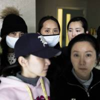 Chinese women who say they have been left disfigured by shoddy cosmetic surgeries in South Korea wait at a clinic in Beijing on Feb. 4. While China's domestic plastic surgery market is worth tens of billions of dollars, persistent safety concerns are driving growing numbers of people into seeking cosmetic procedures abroad. | AFP-JIJI