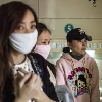Chinese women who say they have been left disfigured by shoddy cosmetic procedures in South Korea wait at a clinic in Beijing on Feb. 4. While China's domestic plastic surgery market is worth tens of billions of dollars, persistent safety concerns are driving growing numbers of consumers abroad. | AFP-JIJI