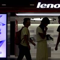 People walk past a Lenovo flagship experience store in Beijing in this file photo. Security researchers revealed Feb. 19 that some computers sold by China's Lenovo, the world's biggest PC maker, had a major security hole that would let any garden-variety hacker impersonate shopping, banking and other websites and steal users' credit card numbers and other personal data. | AP