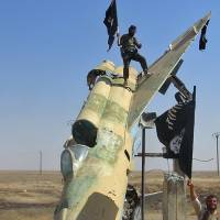 This undated file photo posted in August by the Raqqa Media Center shows Islamic State fighters wave the group's flag from a damaged display of a government fighter jet following the battle for the Tabqa air base, in Raqqa, the jihadi bastion that Syrian Kurds and rebels are now advancing on. | AP