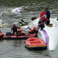 Rescue personnel work to free passengers from a TransAsia ATR 72-600 turboprop plane that crash-landed into a river outside Taiwan's capital Taipei in New Taipei City on Wednesday. The passenger plane with 58 people on board was on a domestic flight when it plunged into the river, with at least 10 people rescued and dozens trapped inside, according to television reports. | AFP-JIJI
