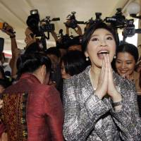 Former Thai Prime Minister Yingluck Shinawatra gives a traditional greeting as she leaves a National Legislative Assembly meeting in Bangkok on Jan. 22. | REUTERS