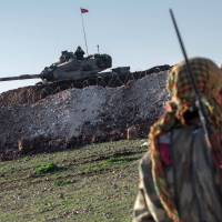 A Syrian Kurdish militia member of YPG patrols near a Turkish Army tank, as Turks work to build a new Ottoman tomb in the background in Aleppo province, Syria, on Sunday.   AP