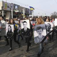People carry portraits of local residents killed in fighting with pro-Russian separatists during a commemoration rally in Kharkiv, Ukraine, on Sunday, when at least two people were killed when a blast struck the rally far from eastern Ukraine's war zone. Kiev said it had arrested suspects who had been armed and instructed in Russia. | REUTERS