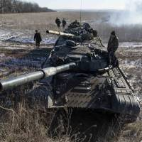 Pro-Russian separatists from the self-proclaimed Donetsk People's Republic stand on top of their tanks at a checkpoint on the road to the town of Debaltseve on Wednesday.   REUTERS