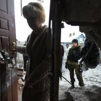 A pro-Russian fighter looks on as a woman enters her home Sunday after it was damaged by shelling the day before in the suburbs of the eastern Ukrainian city of Donetsk. | AFP