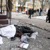 People walk past the body of a victim after shelling Tuesday in the eastern Ukrainian city of Kramotorsk, which is considered to be under firm Kiev control. | AFP-JIJI