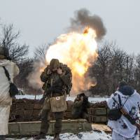 Russian-backed separatists cover their ears as they fire a mortar toward Ukrainian troops outside the village of Sanzharivka, northeast of Debaltseve in eastern Ukraine, on Wednesday. | AP
