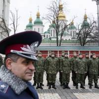 Members of the newly created Ukrainian Interior Ministry battalion 'St. Mary' take part in a ceremony before heading to military training, in front of Kiev's St. Sophia Cathedral on Tuesday. | REUTERS