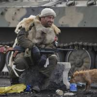A Russian-backed rebel rests as in Debaltseve, Ukraine, on Friday. After weeks of relentless fighting, the embattled Ukrainian rail hub of Debaltseve fell Wednesday to Russia-backed separatists, and the rebels reported taking hundreds of soldiers captive. | AP