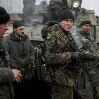 Members of Ukraine's armed forces stand next to their tank on a road not far from Debaltseve, in the east of the country, on Sunday. | REUTERS