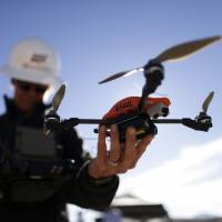 In this Oct. 16, 2014 file photo, former Navy helicopter pilot and San Diego Gas & Electric unmanned aircraft operator Teena Deering holds a drone as it is prepared for takeoff near Boulevard, California. | AP