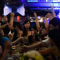 Youngsters drink beer at a local open-air bar in downtown Ho Chi Minh City in December. A new crop of beer clubs is raising concern about Vietnam's drinking culture. | AFP-JIJI