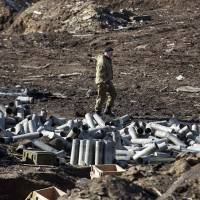 A fighter with the separatist self-proclaimed Donetsk People's Republic army looks for ammunition in a destroyed Ukrainian army compound in the town of Debaltseve on Sunday. | REUTERS