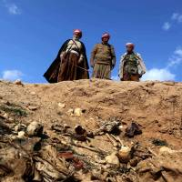 Members of the Yazidi sect peer into a mass grave in the northwestern Sinjar area of Iraq containing the remains of people slaughtered by Islamic State militants, as they search for clues that might lead them to missing relatives. | AFP-JIJI