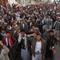 Yemeni supporters of the Shiite Huthi movement take part in a rally to commemorate the fourth anniversary of the start of the uprising that forced out president Ali Abdullah Saleh in Sanaa on Feb.11. Following their takeover in the capital, the Huthi militia seized more territory in the Sunni-majority country last week, sparking fears of a backlash from its feared al-Qaida branch. The banner reads in Arabic: 'God is the greatest... Death to America, death to Israel, cursed be the Jews, victory for Islam.'   AFP-JIJI
