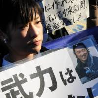 A woman takes part in a memorial service in front of the prime minister's office in Tokyo on Sunday for journalist Kenji Goto, who was slain by Islamic State militants. The sign she holds reads: 'We don't need military force.' | SATOKO KAWASAKI