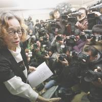 Junko Ishido, mother of Kenji Goto, is mobbed by reporters at her home in Tokyo on Sunday after the release online of a video that showed the Islamic State group's beheading of her son. | AP