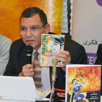 Maher El-Sherbini, a professor of Japanese literature at Cairo University, holds a copy of 'Hadashi no Gen' ('Barefoot Gen') at a signing event in Cairo on Monday. He has translated into Arabic the first of 10 volumes of the celebrated manga. | KYODO