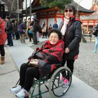 A Japanese tour guide poses with a wheelchair-bound tourist from Thailand at Kiyomizu Temple in Kyoto on Dec. 30. The Buddhist temple is one of many tourist sites undergoing access modifications to help visitors with limited mobility.   KYODO