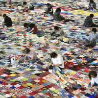 Residents and outside volunteers stitch together donated cloth squares to make a huge quilt in Ishinomaki, Miyagi Prefecture, last September. Guinness World Records has declared it the world's largest blanket. | KYODO