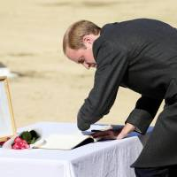 Prince William signs a visitors' book at the Commonwealth War Cemetery in Yokohama on Friday, where he was shown a photograph of his late mother, Princess Diana, during a visit she made to the site. | KYODO