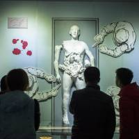 Museum visitors in Harbin, Heilongjiang province, look at a display on Jan. 7 illustrating the inhumane experiments that Japan's Unit 731 allegedly conducted on detainees. | AFP-JIJI