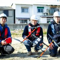 Masato Ono (left), an IT engineer who is leading a project to see whether drones can be used to deliver goods to small islands, poses with the staff of K&S Co. at Takamatsu port, Kagawa Prefecture, in January. | SHINTARO MIYAWAKI/CHUNICHI SHIMBUN