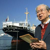 Shigeru Takabayashi, who was a cadet at a branch of the Imperial Japanese Naval Academy in Nagasaki Prefecture from spring to summer 1945, stands in front of the Hikawa Maru cruise liner in Yokohama with the only remaining copy of the academy's English textbook and his diary of that time. | KYODO